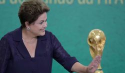 FILE - In this June 2, 2014, file photo, Brazil's President Dilma Rousseff waves to children at a ceremony where FIFA President Sepp Blatter presented the 2014 World Cup trophy to Rousseff at the Planalto presidential palace, in Brasilia, Brazil. President Rousseff has taken to the nation's airwaves Tuesday June 10, 2104, to deliver a pre-taped address trying to rally the nation behind the World Cup that begins this week. (AP Photo/Eraldo Peres,File)
