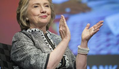 """Former Secretary of State Hillary Rodham Clinton applauds during introductions before addressing the World Bank Group's report """"Voice and Agency: Empowering Women and Girls for Shared Prosperity"""" at World Bank headquarters in Washington, Wednesday, May 14, 2014. The report focuses on pervasive constraints facing women and girls worldwide. (AP Photo/Cliff Owen)"""