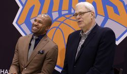 Derek Fisher, left, laughs, while New York Knicks president Phil Jackson speaks during a news conference in Tarrytown, N.Y., Tuesday, June 10, 2014. The Knicks hired Fisher as their new coach on Tuesday, with Jackson turning to one of his trustiest former players. (AP Photo/Seth Wenig)
