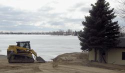 FILE - In this March 19, 2014 file photo, a property owner shores up a dike to ensure protection against the rising of Rice Lake in Minot, N.D.  A district judge has put a stop to plans for a $6 million pipeline to relieve chronic flooding at Rice Lake in north central North Dakota. Judge Richard Hagar says the Rice Lake Recreation Service District doesn't have the authority under state law to use eminent domain to obtain land along the proposed 11.5-mile route of the pipeline to transfer excess lake water into Douglas Creek. (AP Photo/The Minot Daily News, Jill Schramm, File)