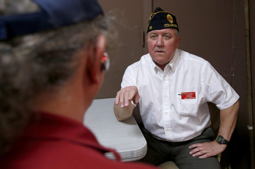 Ralph Bozella, right, chairman of the American Legion National Veterans Affairs & Rehabilitation Commission, speaks with a military veteran as dozens of veterans showed up at a health care crisis center set up by the American Legion at the American Legion Post 1 hall, at a first-of-its-kind event for the nation's largest veterans group, Tuesday, June 10, 2014, in Phoenix. More than 57,000 new applicants have had to wait at least three months before their first appointments, while an additional 64,000 who enrolled for VA health care over the past decade have never been seen by a doctor, according to a VA audit released earlier this week. (AP Photo/Ross D. Franklin)