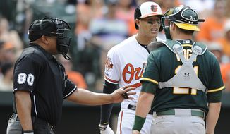In this Sunday, June 8, 2014 photo, home plate umpire Adrian Johnson, left, separates Baltimore Orioles' Manny Machado, left, and Oakland Athletics catcher Stephen Vogt after Machado threw his bat into the infield in the eighth inning of a baseball game in Baltimore. Machado was ejected for throwing the bat and Athletics pitcher Fernando Abad was ejected for throwing at him a second time. The Athletics beat the nOrioles 11-1. (AP Photo/Gail Burton)
