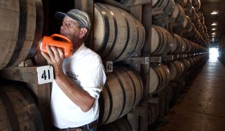 ** FILE ** In this Sept. 2003, file photo, Dewayne Evans checks for leaks in the barrels of whiskey aging in a warehouse at the George Dickel Distillery near Tullahoma, Tenn. (AP Photo/Mark Humphrey, File)