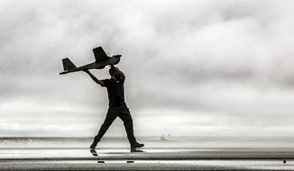 ** FILE ** In this undated photo provided by AeroVironment, a man hand-launches a Puma drone aricraft. The Puma is a small, hand-launched craft about 4 1/2 feet long and with a 9-foot wingspan. It was initially designed for military use. (AP Photo/AeroVironment)