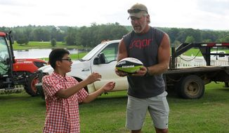 ** FILE ** Retired NFL quarterback Brett Favre Brett Favre gives some passing pointers to Roque Dunagan, 11, on Monday, June 9, 2014 at the farm of actress Sela Ward in Lauderdale County, Miss. (AP Photo/The Meridan Star, Terri Ferguson Smith )