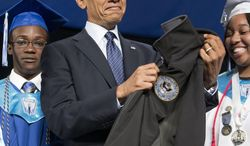 President Barack Obama holds up a fleece jacket that was give to him a gift from the class of 2014 after delivering the commencement address at Worcester Technical High School, Wednesday, June 11, 2014 in Worcester, Mass. (AP Photo/Pablo Martinez Monsivais)