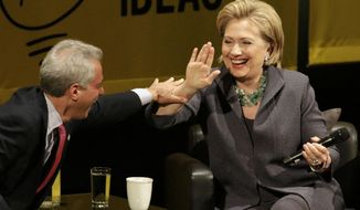 Former Secretary of State Hillary Rodham Clinton laughs with Chicago Mayor Rahm Emanuel after he missed her hand during a high-five attempt, Wednesday, June 11, 2014, in Chicago, during an event promote her new book. (AP Photo/Stacy Thacker)