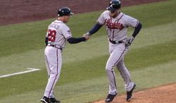 Atlanta Braves third base coach Doug Dascenzo (28) greets Braves' Freddie Freeman as Freeman rounds third base on his solo home run in the fourth inning of a baseball game in Denver on Tuesday, June 10, 2014. (AP Photo/Joe Mahoney)