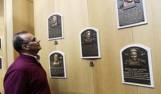 Former New York Yankees manager Joe Torre looks at plaques from the first class of inductees during his orientation visit at the Baseball Hall of Fame on Tuesday, March 25, 2014, in Cooperstown, N.Y. Torre will be inducted to the hall in July. (AP Photo/Mike Groll)