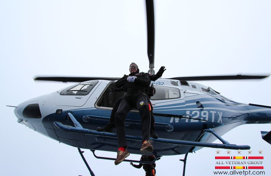 In this photo provided by the All Veteran Parachute Team, former President George H.W. Bush is tethered to Mike Elliott, a member of the All Veteran Parachute Team, on a jump from a helicopter as they celebrate Bush's 90th birthday in Kennebunkport, Maine, Thursday, June 12, 2014. (AP Photo/All Veteran Parachute Team, Charles Cooley)