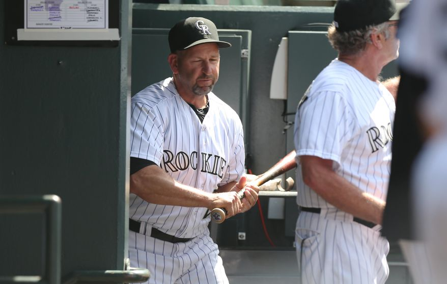 Upset over being ejected from the game, Colorado Rockies manager Walt Weiss grabs a bat on the way to smashing it against the wall in the team's dugout on the way to the showers against the Atlanta Braves in the eighth inning of the Rockies' 10-3 victory in a baseball game in Denver on Thursday, June 12, 2014. Weiss was ejected for arguing after the rockies' Corey Dickerson was hit by a pitch thrown by Braves relief pitcher David Carpenter. (AP Photo/David Zalubowski)