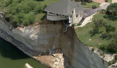 In this image taken from video provided June 12, 2014, by WFAA.Com, a luxury house teeters on a cliff about 75 feet above Lake Whitney in Whitney, Texas. The owner of a vacant luxury house teetering on a crumbling 75-foot cliff over a Central Texas lake has decided to burn the house and clear the lot of the debris. (AP Photo/WFAA.Com)