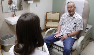 ** FILE ** In this June 12, 2014 file photo, Michael Storemski, right, of Harrah, Okla., talks with Dr. Christina Henson, left, following his treatment at the Veterans Administration Medical Center in Oklahoma City, Thursday, June 12, 2014. (AP Photo/Sue Ogrocki, File)