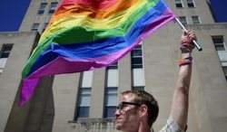 Gary Jones, 37, Racine, holds aloft the rainbow striped gay and lesbian pride flag in front of the Racine County Courthouse on Friday, June 13, 2014, in Racine, Wis., during a rally in support of gay marriage after the county has still refused to grant marriage licenses to same-sex couples despite a judge's ruling that the state ban on gay marriage is unconstitutional. Racine County is one of a minority of counties in Wisconsin currently continuing to refuse to issue marriage licenses to same-sex couples. (AP Photo by Scott Anderson, Journal Times)