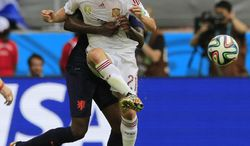 Netherlands' Bruno Martins Indi grabs hold of Spain's David Silva during the group B World Cup soccer match between Spain and the Netherlands at the Arena Ponte Nova in Salvador, Brazil, Friday, June 13, 2014. (AP Photo/Bernat Armangue)