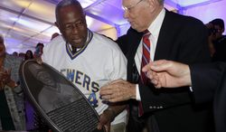 Baseball commissioner Bud Selig presents Hank Aaron with a replica of a plaque that will be displayed on the new Milwaukee Brewers Wall of Honor before a baseball game between the Milwaukee Brewers and the Cincinnati Reds Friday, June 13, 2014, in Milwaukee. (AP Photo/Morry Gash)