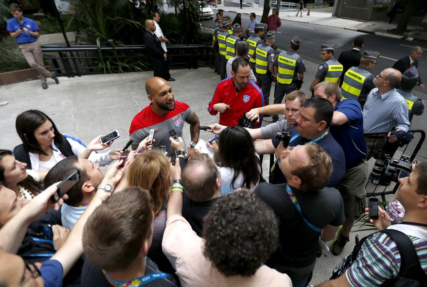 United States goalkeeper Tim Howard, center left, talks to members of the media while military police officers, top right, stand guard outside of the team hotel in Sao Paulo, Brazil, Friday, June 13, 2014.  The U.S. will play in group G of the 2014 soccer World Cup. (AP Photo/Julio Cortez)