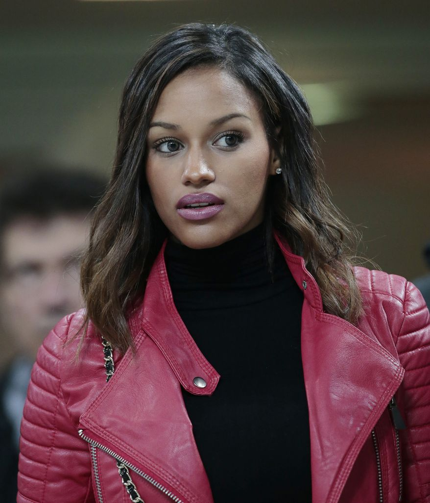 Model Fanny Neguesha waits for the start of a round of 16th Champions League soccer match between AC Milan and Atletico Madrid at the San Siro stadium in Milan, Italy, Wednesday, Feb. 19, 2014 where her fiance Italian forward Mario Balotelli stars. (AP Photo/Emilio Andreoli)