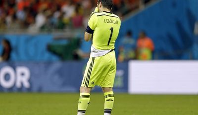 Spain's goalkeeper Iker Casillas wipes his face after being scored on for the fourth time during the second half of the group B World Cup soccer match between Spain and the Netherlands at the Arena Ponte Nova in Salvador, Brazil, Friday, June 13, 2014.  (AP Photo/Natacha Pisarenko)