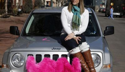 FILE - In this Feb. 28, 2014 file photo, part time Lyft driver Brittany Cameron sits on the hood of her own vehicle, which she uses to give rides, and which is adorned with Lyft's trademark pink mustache, in downtown Denver. Lyft is a transportation network company whose mobile-phone application facilitates peer-to-peer ride sharing by enabling passengers who need a ride to request one from drivers who have a car. Internet companies like Lyft that connect riders to drivers with a few taps on a cellphone app will be regulated in Colorado with legislation soon to become law, putting the state at the forefront of a push to try to legitimize the flourishing tech startups. (AP Photo/Brennan Linsley)