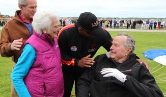 In this photo provided by the All Veteran Parachute Team, former President George H.W. Bush, right, is congratulated on his parachute jump by his son, former President George W. Bush, far left, his wife Barbara Bush and his tandem team partner Mike Elliott on his 90th birthday in Kennebunkport, Maine, Thursday, June 12, 2014. (AP Photo/All Veteran Parachute Team, Kenneth Wasley) ** FILE **
