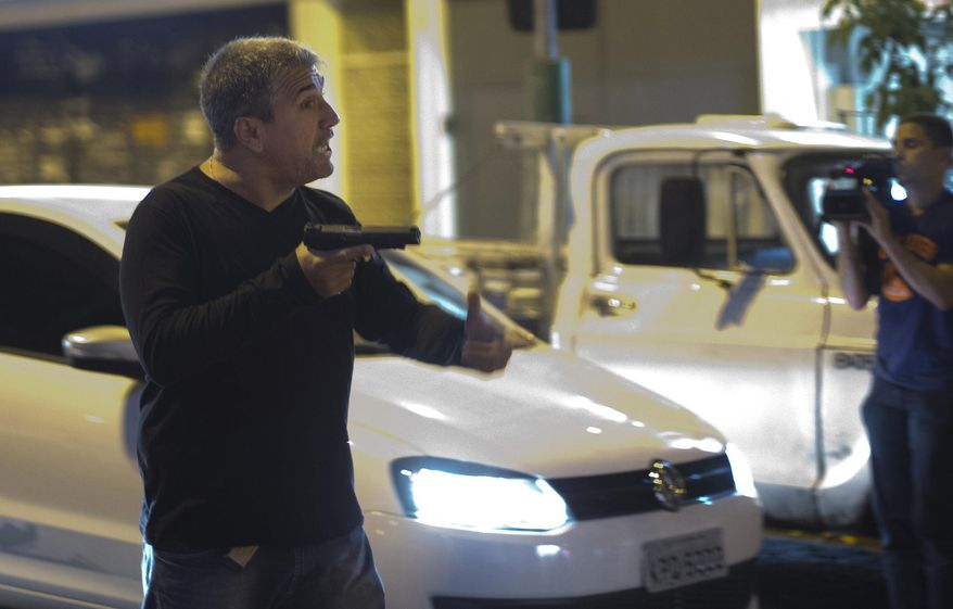 A man who identified himself as a police officer points his gun at anti-World Cup protesters blocking a road that leads to the Maracana stadium in Rio de Janeiro, Brazil, Sunday, June 15, 2014. The man told people not come any closer to him, and fired shots into the air which dispersed the crowd. He then continued shooting from a car driven by another person as they left the scene. (AP Photo/Silvia Izquierdo)