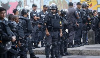 Police guard the streets near the Maracana stadium before the game between Argentina and Bosnia during the 2014 soccer World Cup in Rio de Janeiro, Brazil, Sunday, June 15, 2014. (AP Photo/Silvia Izquierdo)