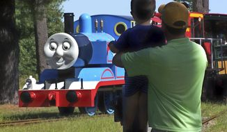 In this 2012 photo provided by Edaville USA, a father and son watch Thomas the Tank Engine roll down the track at an annual Day Out with Thomas event at the Edaville USA theme park in Carver, Mass. Groundbreaking for the first permanent Thomas Land in the the United States is set for July 2014 at Edaville USA, and is expected to be open for business in the summer of 2015. (AP Photo/Edaville USA)