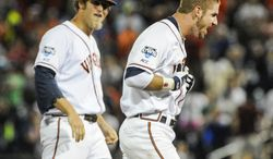 Virginia's Mike Papi, right, and teammate Austin Young, celebrate after Papi hit a double in the ninth inning against Missisippi that scored Thomas Woodruff to win an NCAA baseball College World Series game in Omaha, Neb., Sunday, June 15, 2014. Virginia won 2-1. (AP Photo/Eric Francis)
