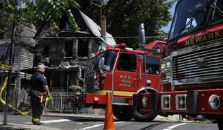 Firefighters work near the rubble of a burned out home as they look for clues to a fire that authorities say killed six people in Newark, N.J., Sunday, June 16, 2014. The Essex County prosecutor's office says the fast-moving fire that roared through a single-family home in New Jersey's largest city, broke out at around 4 a.m. Sunday. Authorities say it appears some of the victims are related. (AP Photo/Mel Evans)