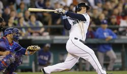 Seattle Mariners' Kyle Seager doubles in a pair of runs against the Texas Rangers in the fifth inning of a baseball game on Sunday, June 15, 2014, in Seattle. (AP Photo/Elaine Thompson)
