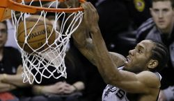 San Antonio Spurs forward Kawhi Leonard (2) dunks against the Miami Heat during the first half in Game 5 of the NBA basketball finals on Sunday, June 15, 2014, in San Antonio. (AP Photo/Tony Gutierrez)