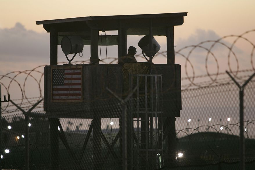 FILE - In this Dec. 7, 2006 file photo reviewed by the U.S. Military, a U.S. soldier keeps watch from a guard tower overlooking Camp Delta detention center on Guantanamo Bay U.S. Naval Base in Cuba. Lawyers for Guantanamo prisoners charged in the Sept. 11 attack say the FBI has questioned more people who work as support staff on their legal teams than previously disclosed, a development that may prompt a new detour in an already snarled case when the war crimes tribunal reconvenes Monday at the U.S. base in Cuba. A judge will consider a delay in the proceedings in a hearing on Monday, June 16, 2014. (AP Photo/Brennan Linsley, File)