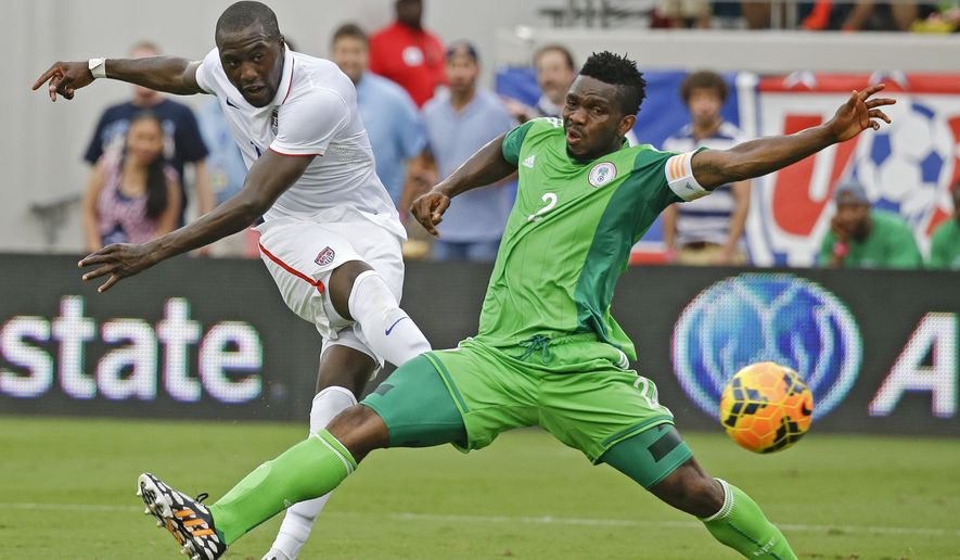 United States's Jozy Altidore, left, scores a goal as he kicks the ball past Nigeria's Joseph Yobo, right, during the second half of an international friendly soccer match in Jacksonville, Fla., Saturday, June 7, 2014. The United States won 2-1. (AP Photo/John Raoux)