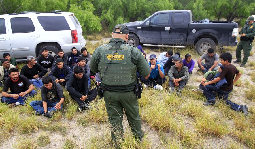 ** FILE ** In this Thursday, April 17, 2014, photo, immigrants suspected of being in the country illegally sit in a group after U.S. Border Patrol agents detained at least 80  immigrants who'd been living in a makeshift encampment in suburban McAllen, Texas. (AP Photo/The Monitor, Gabe Hernandez)