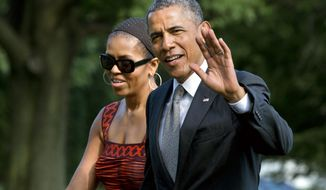 ** FILE ** President Barack Obama waves as he walks with first lady Michelle Obama on their return to the White House from a trip to California, Monday, June 16, 2014, in Washington. (AP Photo/Jacquelyn Martin)
