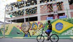 A cyclist makes his way down a street decorated with images celebrating the 2014 soccer World Cup in Fortaleza, Brazil, Monday, June 16, 2014.  (AP Photo/Marcio Jose Sanchez)