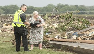 Ruth Labenz is assisted to safety by a Stanton County Sherriff's officer after her home was destroyed by tornadoes in the town of Pilger, Neb., Monday, June 16, 2014. (AP Photo/Mark 'Storm' Farnik)