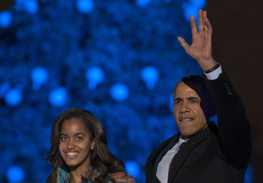 **FILE** As they arrive, President Barack Obama and his daughter Malia look to the audience during the 2013 National Christmas Tree Lighting ceremony at the Ellipse in Washington on Dec. 6, 2013. (Associated Press)