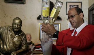 FILE - This July 21, 2012 file photo shows bartender Alejandro Bolivar preparing a daiquiri at El Floridita tavern in Old Havana, Cuba, to honor the 195th anniversary of the bar and the anniversary of the birth of its most famous frequent customer, novelist Ernest Hemingway, of whom a life-sized sculpture sits barside. Legend has it that Hemingway once downed 13 doubles in one sitting. There are sites connected to Hemingway in many different locales including Florida, Cuba, Arkansas, Idaho and Illinois.  (AP Photo/Franklin Reyes, File)