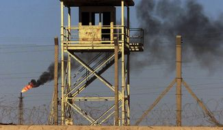 File - In this Monday, Oct. 6, 2003 file photo, an abandoned watchtower and lines of barbed wire are seen surrounding Iraq's largest oil refinery as smoke rises from a petroleum gas flare, in the city of Beiji, north of Baghdad. On Wednesday, June 18, 2014, a top Iraqi security official said Islamic militants of the al-Qaida-inspired Islamic State of Iraq and the Levant laid siege to Iraq's largest oil refinery late Tuesday night, threatening a facility key to the country's domestic supplies as part of their ongoing lightning offensive across the country. The Beiji refinery accounts for a little more than a quarter of the country's entire refining capacity and any lengthy outage at Beiji risks long lines at the gas pump and electricity shortages, adding to the chaos already facing Iraq. (AP Photo/Ivan Sekretarev, File)