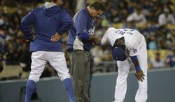 Los Angeles Dodgers manager Don Mattingly, left, watches as Hanley Ramirez, right, is tended to by trainer Stan Conte after Ramirez hurt his hand during the seventh inning of a baseball game against the Colorado Rockies on Tuesday, June 17, 2014, in Los Angeles. (AP Photo/Jae C. Hong)