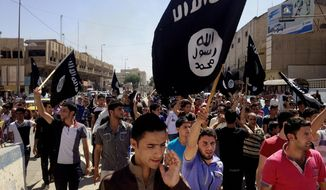 ** FILE ** In this Monday, June 16, 2014, file photo, demonstrators chant pro-al-Qaeda-inspired Islamic State of Iraq and the Levant  as they carry al Qaeda flags in front of the provincial government headquarters in Mosul, 225 miles (360 kilometers) northwest of Baghdad, Iraq. (AP Photo, File)