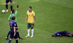 Australia's Tim Cahill, center, is booked by referee Djamel Haimoudi from Algeria, left, after tackling Netherlands' Bruno Martins Indi during the group B World Cup soccer match between Australia and the Netherlands at the Estadio Beira-Rio in Porto Alegre, Brazil, Wednesday, June 18, 2014.  (AP Photo/Michael Sohn)