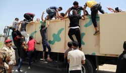 In this June 14, 2014, photo, Iraqi men board a military truck to join the Iraqi army at the main recruiting center in Baghdad, Iraq, after authorities urged Iraqis to help battle insurgents. U.S. spy agencies are scrambling to close intelligence gaps as they seek to support possible military action against the leaders of the al-Qaida-inspired militant group that has seized parts of Iraq. Intelligence officials are trying to provide options for President Barack Obama as he considers how to counter an insurgency he says poses a threat to Americans.(AP Photo/Karim Kadim, File)