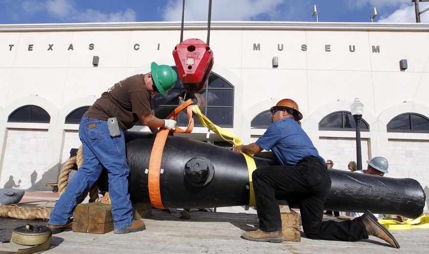 Jimmy Yancey, left, and Rene Del Bosque, both with Domac Inc., secure strapping around the the 11-foot long, 8,400 pound Dahlgren gun as they move it to the Texas City Museum on Wednesday June 18, 2014, in Texas City, Texas.  A Civil War cannon from the 1863 sinking of the USS Westfield has a new resting place at a Texas museum just miles from where the ship went down.   Officials at the Texas City Museum on Wednesday welcomed the restored 12-foot cannon for a maritime exhibit. (AP Photo/The Galveston County Daily News, Jennifer Reynolds) MANDATORY CREDIT; MAGS OUT; TV OUT