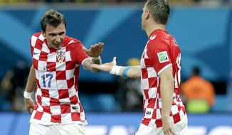 Croatia's Mario Mandzukic, left, celebrates with Croatia's Ivica Olic after scoring his side's third goal during the group A World Cup soccer match between Cameroon and Croatia at the Arena da Amazonia in Manaus, Brazil, Wednesday, June 18, 2014.   (AP Photo/Themba Hadebe)