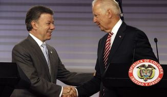 U.S. Vice President Joe Biden, right, shakes hands with Colombia's President Juan Manuel Santos after giving a joint news conference at the presidential palace in Bogota, Colombia, Wednesday, June 18, 2014. Biden met with Santos just three days after the Colombian president won re-election in what was widely seen as an endorsement of talks to end the Western Hemisphere's last sizable armed conflict. (AP Photo/Javier Galeano)