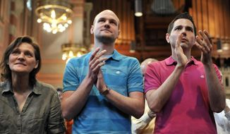 In this June 14, 2014 photo, Brigitte Schaefer, left, her son Tim Schaefer, center, and Tim's partner, John Duncan, applaud as Frank Schaefer receives an Open Door Award for his public advocacy in Massachusetts, at Old South Church, in Boston. Frank Schaefer, a Methodist pastor who was defrocked for officiating his son Tim's wedding to another man, accepted the award the weekend before a Methodist judicial panel was scheduled to hear his appeal to continue in the ministry. (AP Photo/Josh Reynolds)