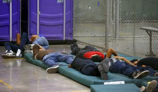 Young boys sleep in a holding cell where hundreds of mostly Central American immigrant children are being processed and held at the U.S. Customs and Border Protection Nogales Placement Center on Wednesday, June 18, 2014, in Nogales, Ariz.  CPB provided media tours Wednesday of two locations in Brownsville, Texas, and Nogales, that have been central to processing the more than 47,000 unaccompanied children who have entered the country illegally since Oct. 1. (AP Photo/Ross D. Franklin, Pool)
